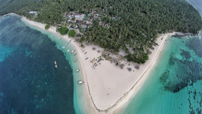 An aerial shot of Daku Island with a glimpse of the small community on it.